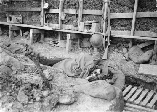 An Australian soldier sleeps wrapped in an overcoat in the trenches in the Bois Greneir sector (AWM EZ0052).