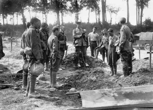 A chaplain reads the burial service beside the grave of a fallen Australian in a cemetery near a casualty clearing station (AWM EZ0064).