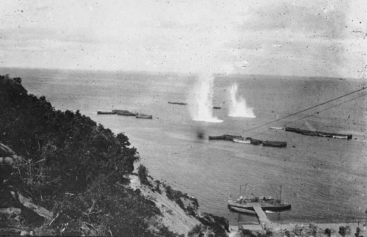 Looking seaward from the heights above Anzac Beach, Turkish shells burst in the water close to Australian Army boats (AWM H03569.