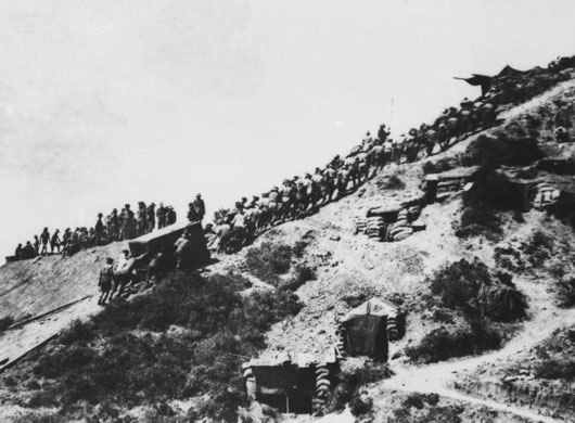 A fatigue party of Maori and Australian soldiers dragging a large water tank uphill from Anzac Cove (AWM C01812).