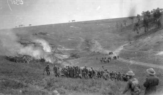 Captured German soldiers rush past Susan Wood, under fire from their own artillery (AWM E03017).