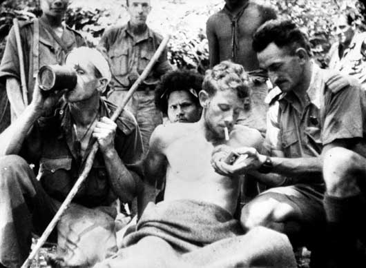 A wounded Australian soldier has his cigarette lit by Salvation Army Chaplain Albert Moore (AWM 013287).