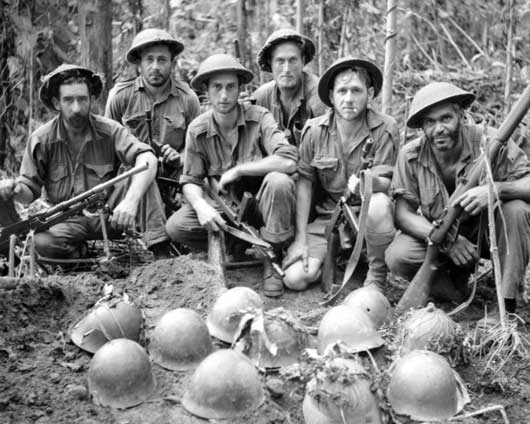 An Australian burying party, with Japanese helmets, placed on top of a common grave (AWM 013645).