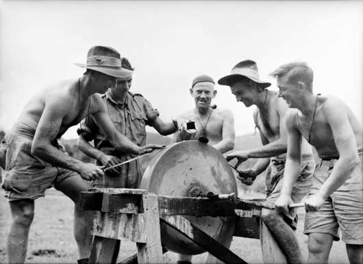 Men of the 2/14th Infantry Battalion sharpen their bayonets in preparation for battle (AWM 026261).