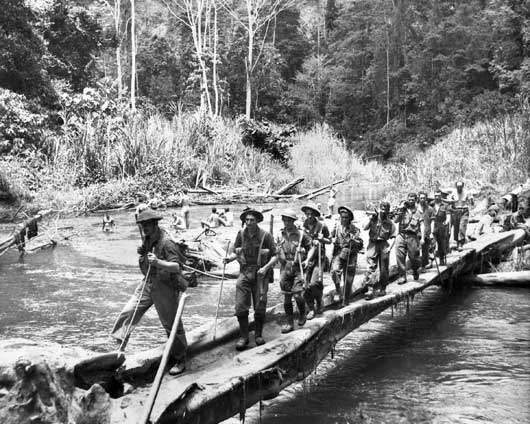 A patrol of Australian infantrymen crossing the Brown River by means of a bridge constructed from a fallen tree, on their way forward to Menari (AWM 027060).