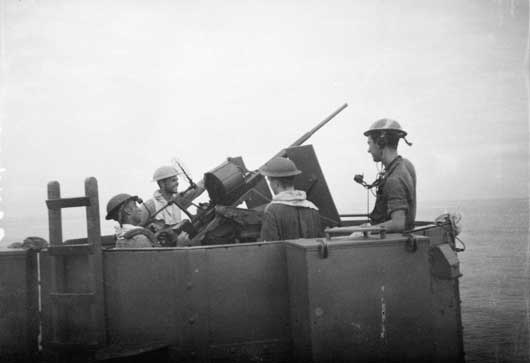 An Oerlikon gun crew on board HMAS Kanimbla preparing to fire on enemy aircraft in Lingayen Gulf (AWM 134255).