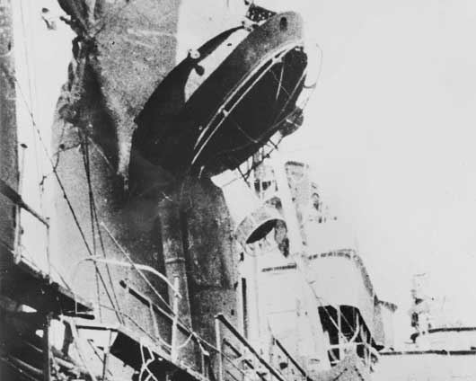 Close up view of damage to the fore funnel of HMAS Australia caused by a Japanese Kamikaze attack during the Battle of Lingayen Gulf (AWM P02018.345).