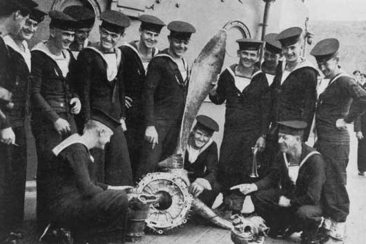 Some of the crew of HMAS Australia examining the propeller of a Japanese Kamikaze plane, which crashed into the ship during the Battle of Lingayen Gulf (AWM P02018.346).