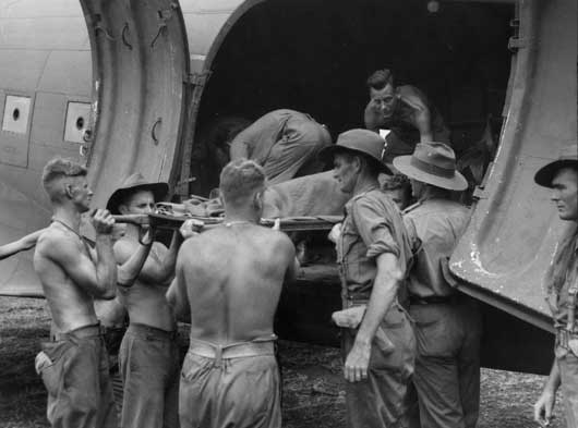 A wounded Australian being loaded into an aircraft for transport back to a base hospital (AWM 057015).