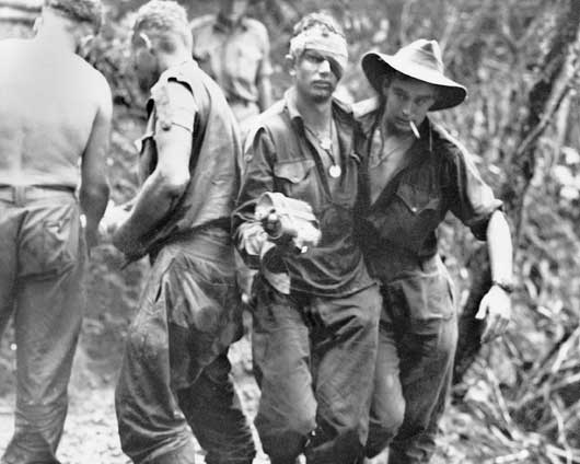 A wounded soldier of the 2/16th Australian Infantry Battalion being assisted to the regimental aid post during the attack on Shaggy Ridge (AWM 062294).