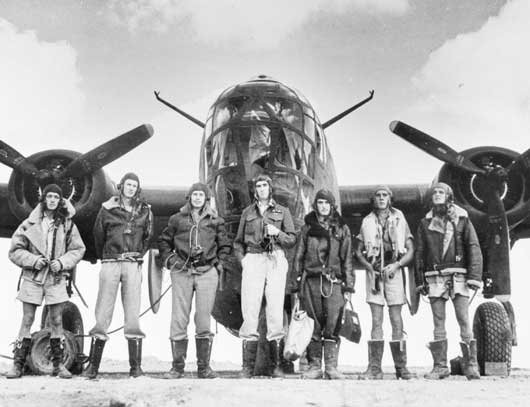Group portrait of an Australian Liberator crew standing in front of their aircraft at an airfield in North Africa (AWM MED1561).