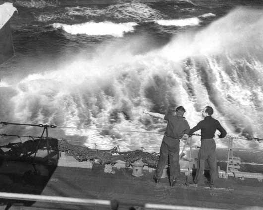 Two crewmembers of HMAS Perth watching the effect on the sea of the ship travelling at high speed (AWM 006614).