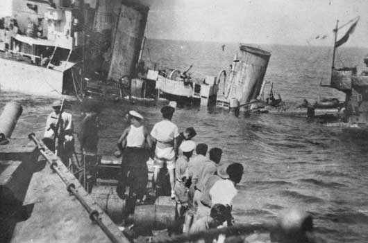 Men aboard HMAS Vendetta look on as the British destroyer HMS Defender goes down off Tobruk (AWM P00090.041).