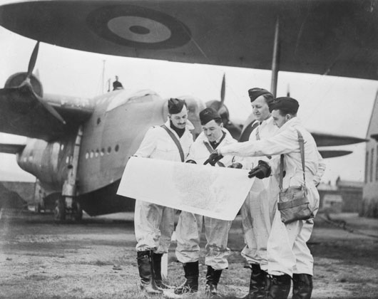 Four of the original Sunderland captains of 10 Squadron RAAF checking flight plans prior to a mission over the Atlantic (AWM 128163).