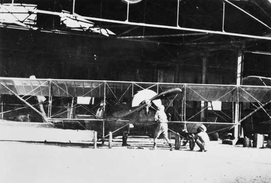 Two unidentified air mechanics working on a Caudron aircraft in a hanger, used by the Half Flight in Mesopotamia (AWM A04131).