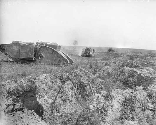 Two tanks on their way into action during the attack on Messines Ridge, as shells burst in the background (AWM E01419).