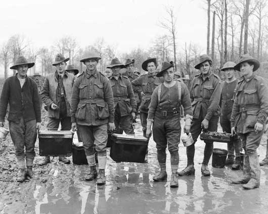 Mess orderlies of an Australian unit conveying hot soup to reserve troops near Hyde Park Corner, in the Messines Sector (AWM E01512).