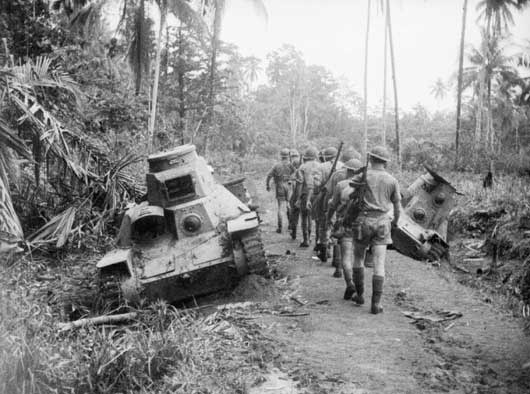 An Australian infantry section passing Japanese light tanks knocked out at Milne Bay (AWM 013320).