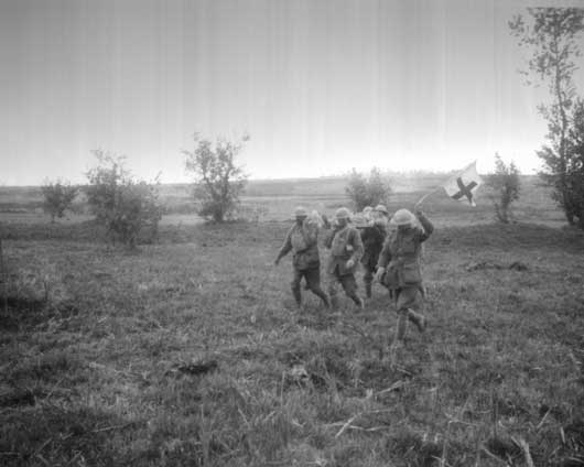 Stretcher bearers of the 6th Australian Infantry Brigade bringing in an injured soldier (AWM E03105).