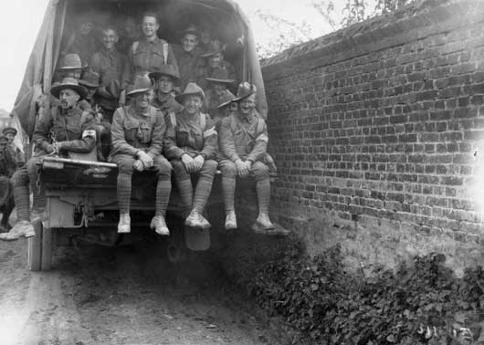 Men of the 6th Australian Field Ambulance pass through the village in a motor lorry, on their way to assist the Medical Services in fighting line (AWM E03130).