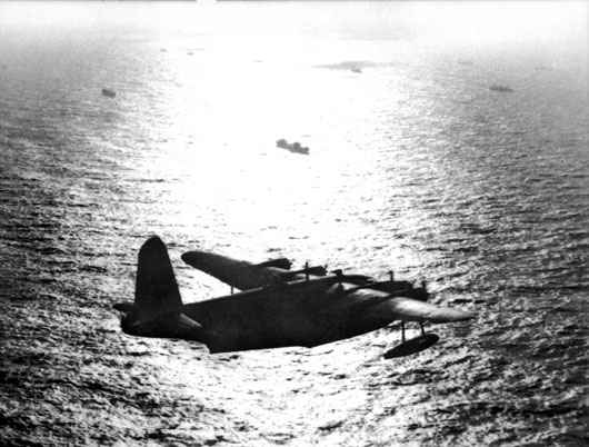 A Sunderland of Coastal Command keeps watch over a convoy as evening falls over the Atlantic (AWM SUK14445).