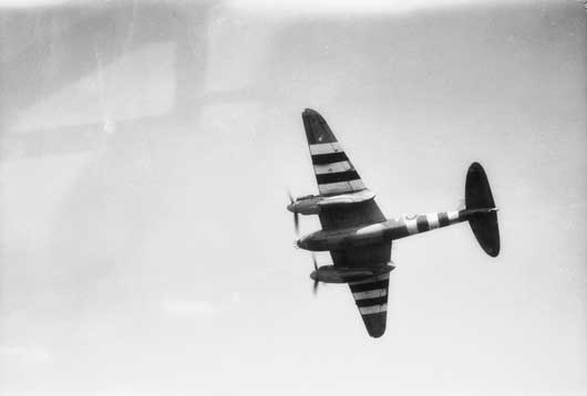 A view of a 464 Squadron RAAF Mosquito aircraft, displaying its invasion markings as it flies over England on its way to attack enemy targets in Normandy (AWM UK1755).