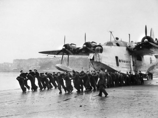Maintenance crews of 10 Squadron RAAF haul a Sunderland ashore into a hanger for overhaul (AWM SUK14702).