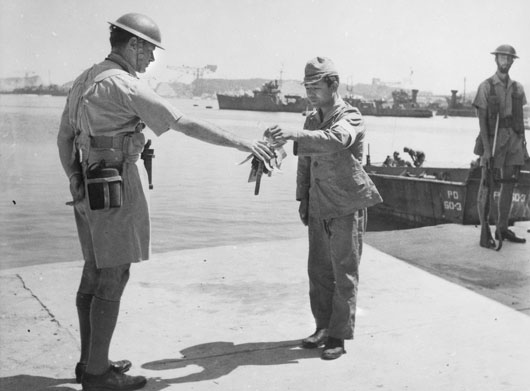 A Japanese official hands over the keys of the Yokosuka Naval Base as a token of surrender, to Commander of the British Landing Forces, Captain H.J. Buchanan of Melbourne, Victoria (AWM 019422).