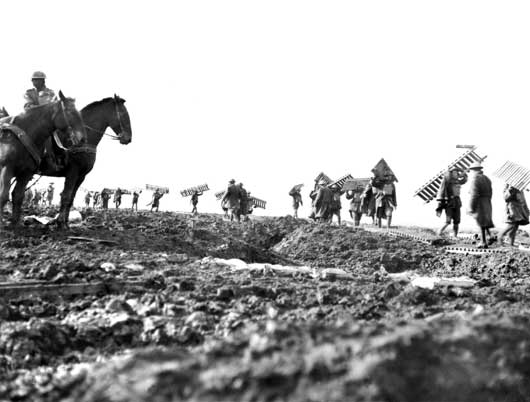 Pioneers of the 1st Division preparing a duckboard track over the muddy waste near Zonnebeke (AWM E00837).