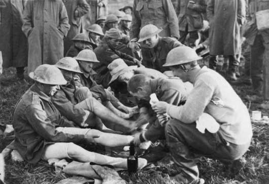 Men of the 40th Battalion having their feet attended to at Dragoon Farm, after several days' fighting in the mud at Passchendaele (AWM E00939).