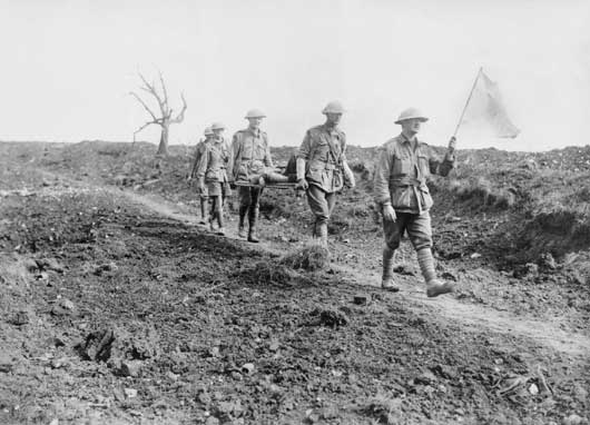 Stretcher bearers of the 6th Australian Infantry Brigade, under the Red Cross Flag, passing the old cemetery of Pozieres (AWM E04946).