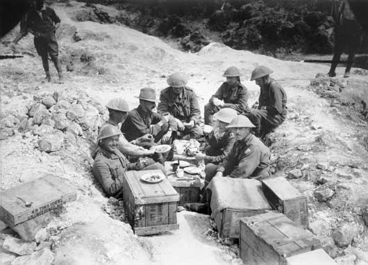 A group of Australian officers having breakfast in a shell hole in Sausage Valley in the forward area (AWM EZ0075).