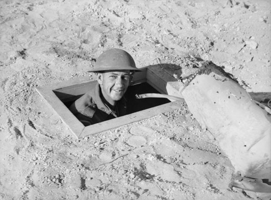 Foxholes dug in the desert often provided the only cover from enemy air raids and artillery barrages (AWM 004952).