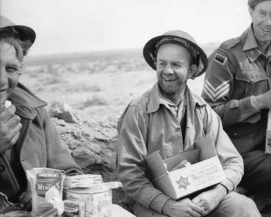 Men of the 2/2nd Battalion holding comforts funds issued on Christmas Day, camped between Sollum and Bardia (AWM 004953).
