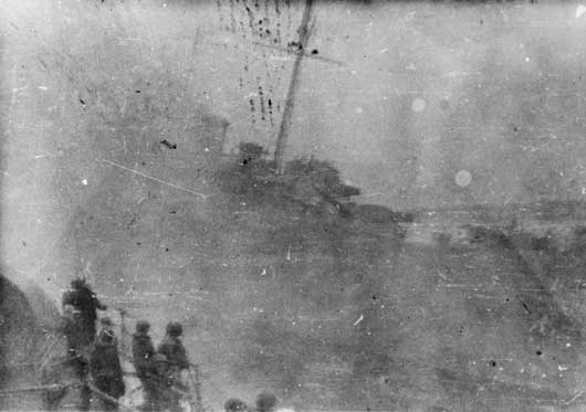 Port bow view of HMAS Canberra sinking, taken from one of the US Navy destroyers in the Battle of Savo Island (AWM P04992.012).