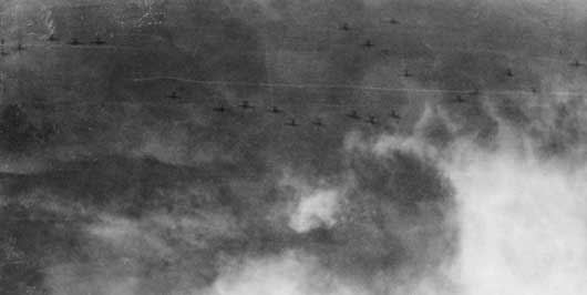 24 Japanese high level bombers, silhouetted against heavy cloud, preparing to unload over a convoy of Allied vessels during the Battle of Savo Island (AWM P05292.008).