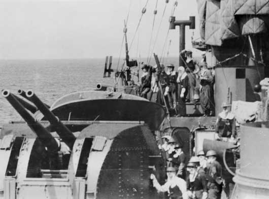 Anti-aircraft gun crews wearing flash protection clothing on board HMAS Canberra, on the lookout for high level bombers (AWM P05292.014).