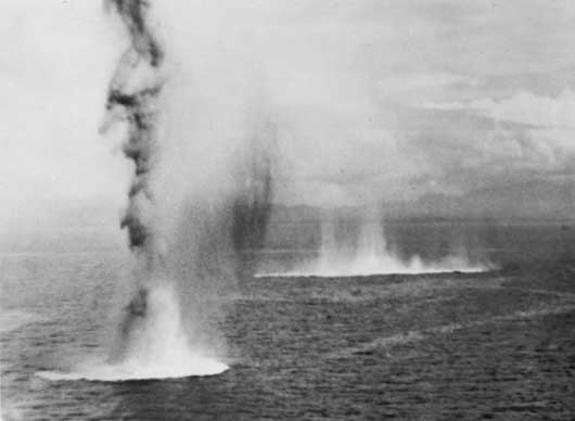 Bombs hitting the water off the island of Guadalcanal, during the Battle of Savo Island (AWM P05292.030).