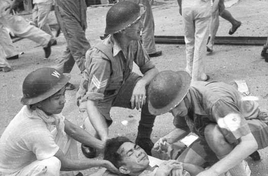 First aid helpers attending injured civilians in a city street after bombing in a Japanese air attack (AWM 011529/10).