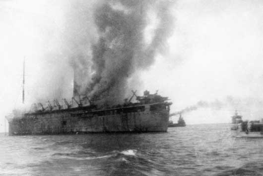 A view of the extensively damaged British transport the Empress of Asia, set on fire during a bombing attack by Japanese aircraft (AWM P01604.001).