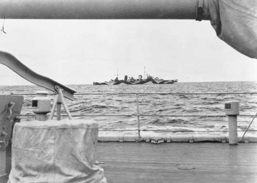 A view of HMAS Perth, taken from HMAS Adelaide as the Perth proceeds northward to join allied naval forces in the Netherlands East Indies (AWM 128105).