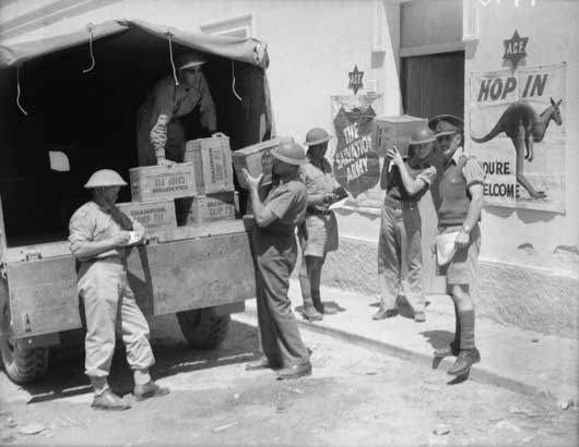 Salvation Army and AIF personnel loading comforts fund items on to a truck for distribution to the troops (AWM 007478).