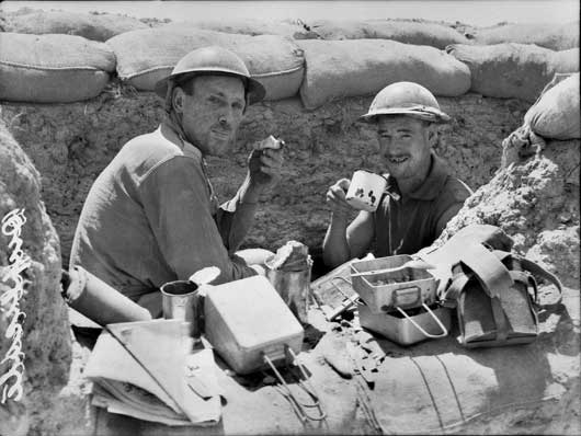 Lance Corporal Frank Smith and Corporal W. Brownrigg of the 2/23rd Infantry Battalion eating lunch whilst on watch in a fire bay (AWM 020502).