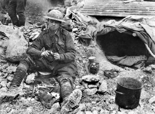 Private A.G. Townsend, 46th Battalion, making a meal of vegetables salvaged from a ruined garden (AWM E02185).