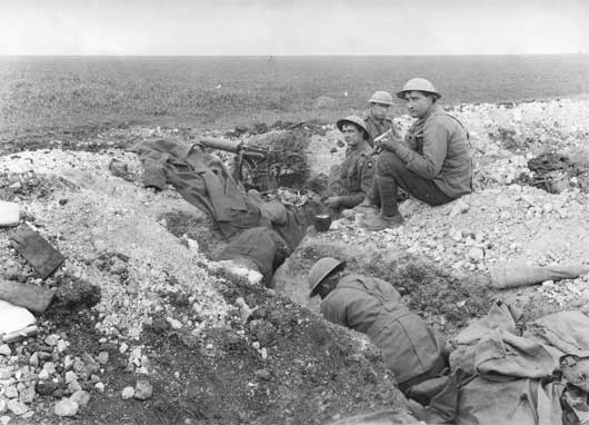Meal time at a machine gun post of the 5th Australian Machine Gun Battalion on Hill 104 (AWM E02296).