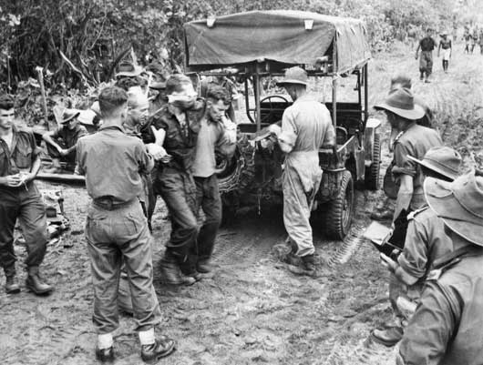 A wounded Australian soldier being helped to a jeep-ambulance on a forward track in Aitape Sector, New Guinea (AWM 018290).