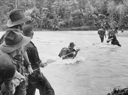 Australian soldiers negotiating a flooded river close to But aerodrome, Aitape Sector (AWM 018294).