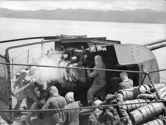 The crew of the 4-inch twin guns aboard the RAN vessel HMAS Swan laying down a barrage on Japanese positions between Aitape and Wewak (AWM 079323).
