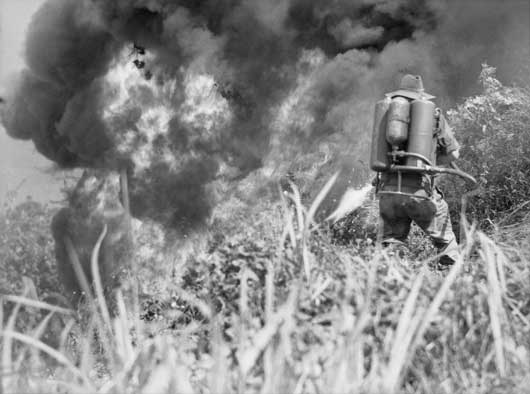 Private A.L. Willett, 2/8 Infantry Battalion, using a flame thrower in the action against the Japanese (AWM 091749).