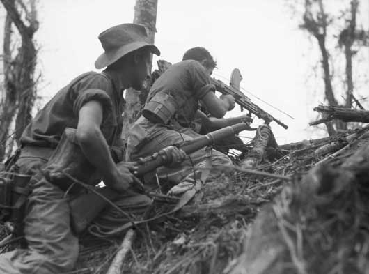 Members of C Company, 2/8 Infantry Battalion, giving covering fire against Japanese positions on Mount Shiburangu (AWM 093451).